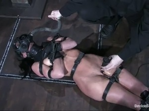 Tied up brunette with a gas mask on her head gets toyed